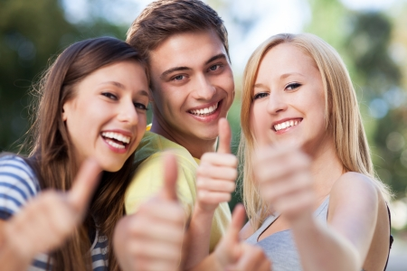 Young people showing thumbs up photo
