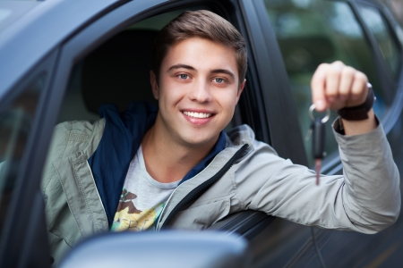 car driver: Young man sitting in car holding car keys