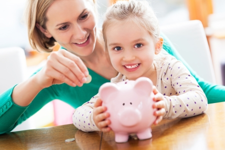 bank interior: Mother and daughter putting coins into piggy bank