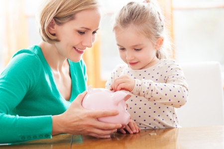 Mother and daughter putting coins into piggy bank photo