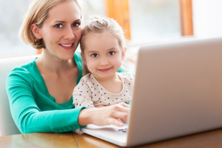 Mother and daughter using laptop photo
