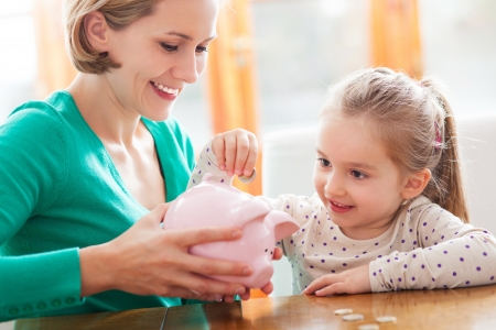bank interior: Mother and daughter with piggy bank