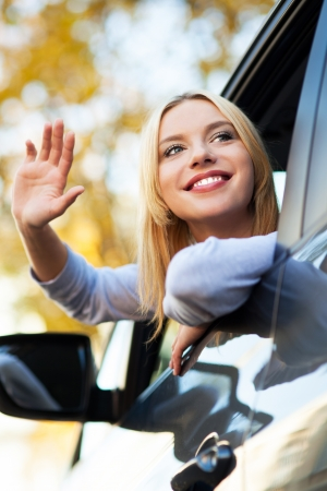 new car: Woman waving from car window Stock Photo