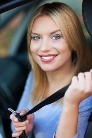 Woman attaching seat belt in car Stock Photo