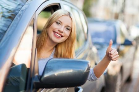 Junge Frau macht thumps-up im Auto