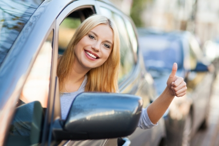 Young woman doing thumps-up in car Stock Photo - 16366732