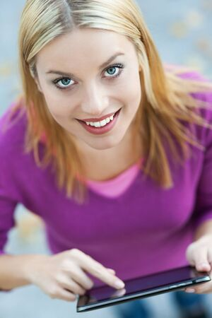 pointing device: Young woman using digital tablet Stock Photo