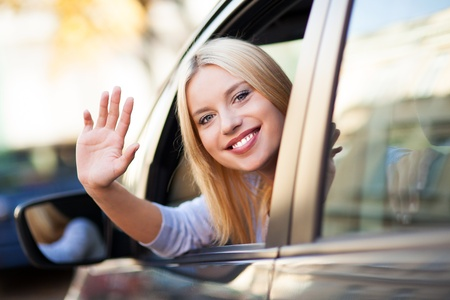 Young woman waving from car window Stock Photo - 16366741