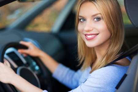 chofer: Mujer sonriente sentado en el coche Foto de archivo