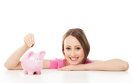 putting in: Young woman putting money in piggy bank