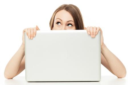 desconfianza: Mujer que mira hacia fuera de detr�s de una computadora port�til Foto de archivo