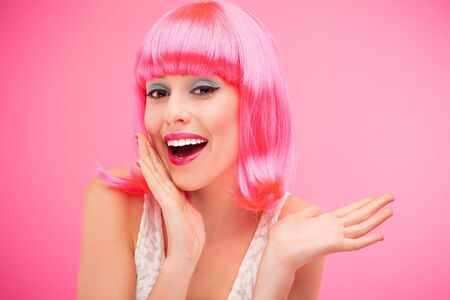 toothy smile: Beautiful woman wearing pink wig Stock Photo