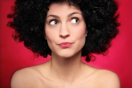 suspicious: Woman with afro wig looking to the side Stock Photo