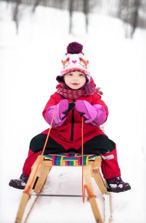sledding: Little girl on sled Stock Photo
