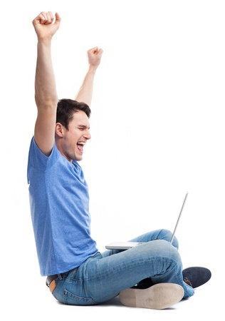 clenching fists: Excited young man using laptop