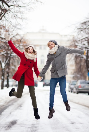 outerwear: Couple jumping in snow
