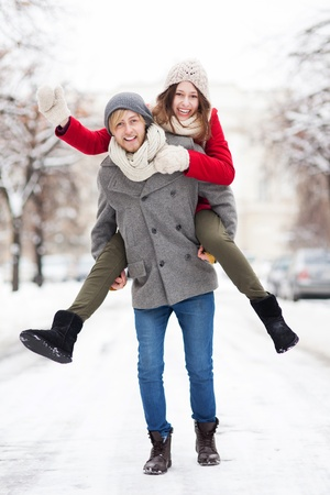 Man giving woman piggyback in winter setting photo