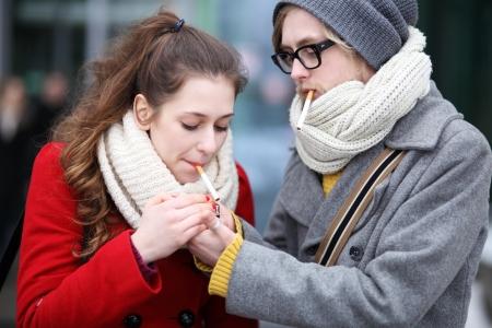 persona fumando: Pareja joven con cigarrillos