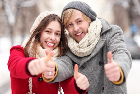 Winter couple with thumbs up photo