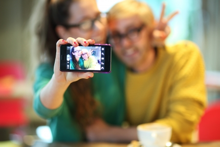 Couple taking self portrait, focus on camera photo