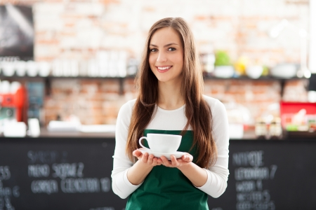 business owner: Waitress holding cup of coffee in cafe Stock Photo