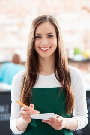 jasschort: Jonge serveerster die blocnote in cafe