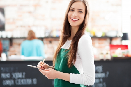 negocios comida: Camarera joven con bloc de notas en el caf�