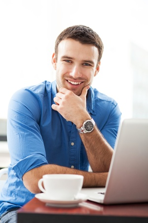 Young man using laptop in cafe photo