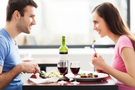 hombre comiendo: Pares que tienen comida en el restaurante Foto de archivo