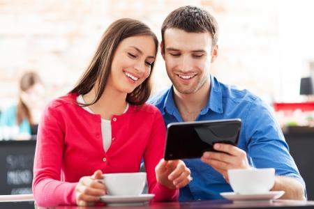 disfrutar: Pareja con tableta digital en el caf�