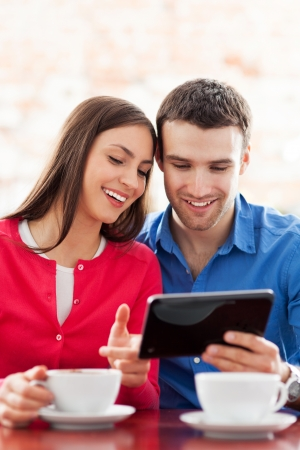 Couple using digital tablet in cafe photo