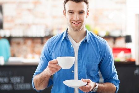 man drinking coffee: Man holding cup of coffee in cafe