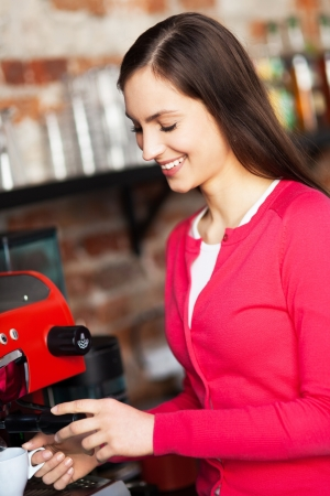 with coffee maker: Female barista by coffee maker