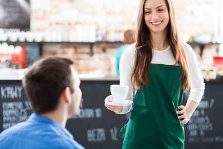 Waitress serving man coffee photo