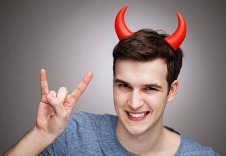 devil horns: Man wearing devil horns