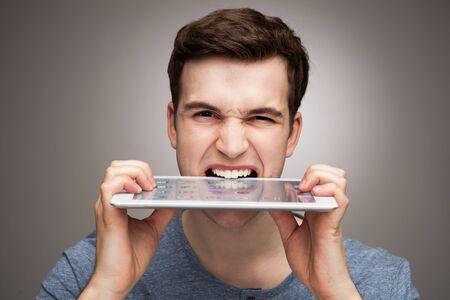 biting: Man biting digital tablet