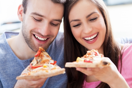 eating pizza: Couple eating pizza