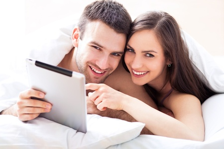 Couple in bed using digital tablet photo