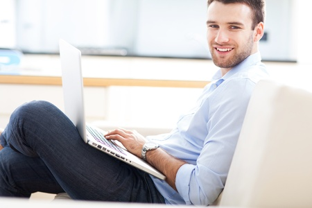Man on sofa with laptop photo