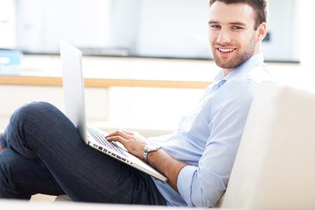 Man on sofa with laptop Stock Photo - 19328702