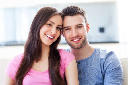 young couple smiling: Young couple on sofa