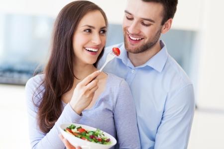woman eat: Couple eating salad Stock Photo