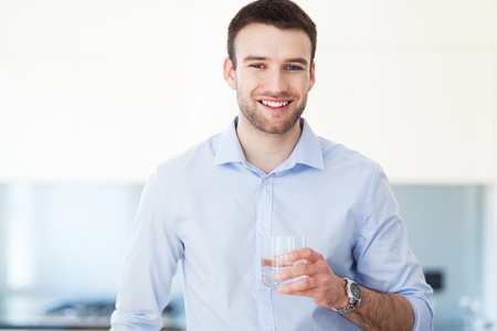 man with glasses: Man in kitchen with glass of water