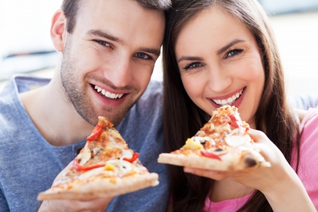 woman eat: Couple eating pizza