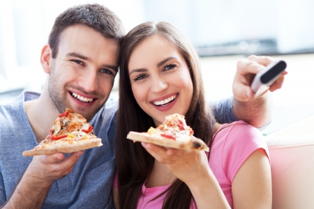 Pareja con pizza y control remoto del televisor photo