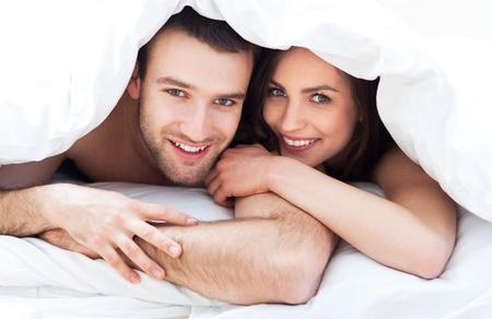 couple au lit: Jeune couple au lit Banque d'images