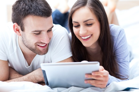 Couple with digital tablet lying on bed photo