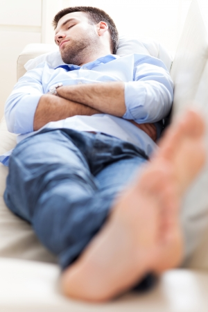 attractive couch: Man sleeping on sofa