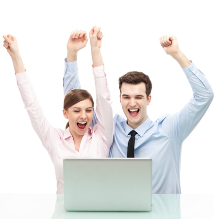 Couple in front of laptop with arms raised photo