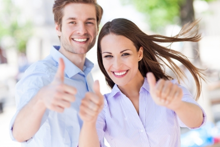 thumbs up man: Young couple showing thumbs up Stock Photo